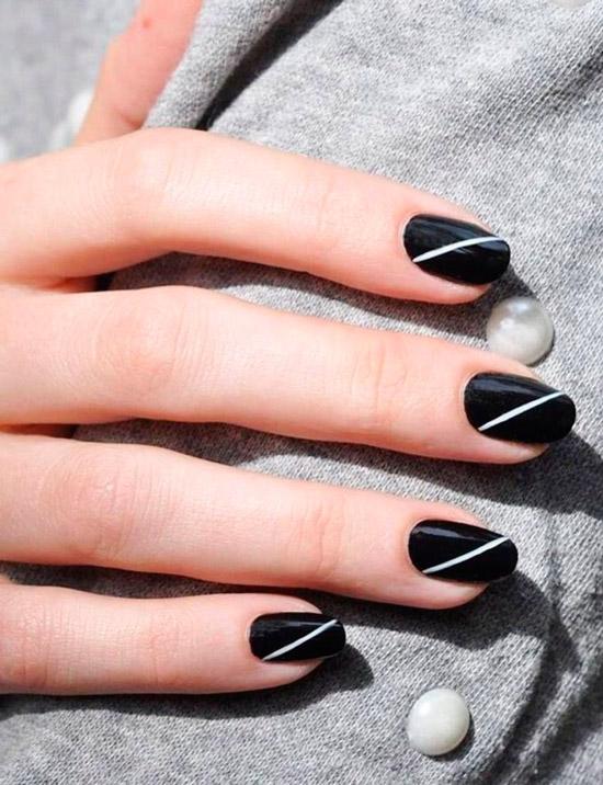 Черный глянцевый маникюр на овальных ногтях с простой белой полосой
