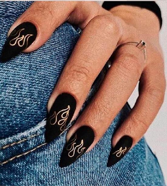 Черный матовый маникюр с золотыми узорами на длинных овальных ногтях