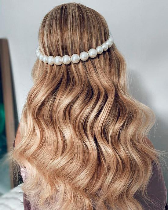 Девушка с длинными светлыми волосами с легкими волнами, волосы украшает повязка из крупного жемчуга