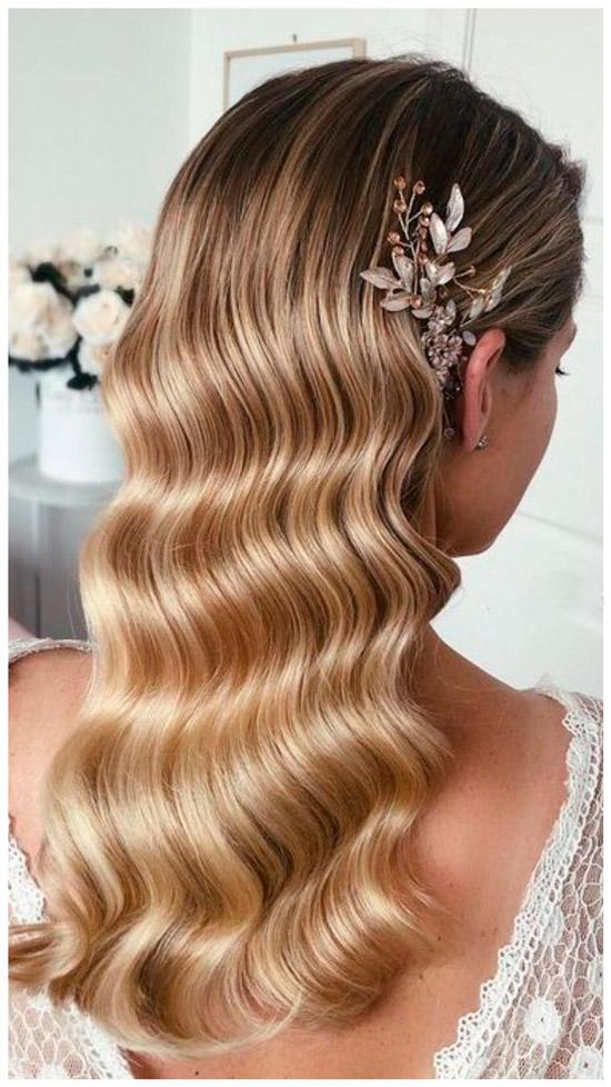 Девушка с изысканными волнами на светлых волосах, украшенные заколкой с цветами