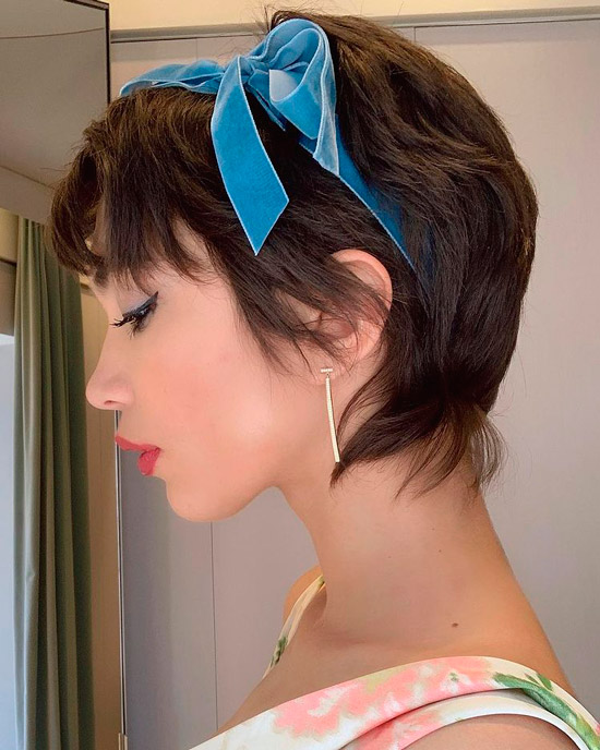 Девушка с короткой прической писки на натуральных волосах, украшенные голубой лентой