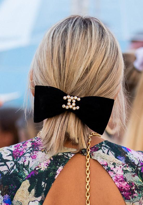 Девушка с короткой стрижкой боб на светлых волосах с черным большим бантом
