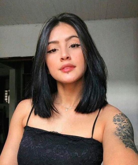 Девушка с красивыми черными волосами с пробором по середине