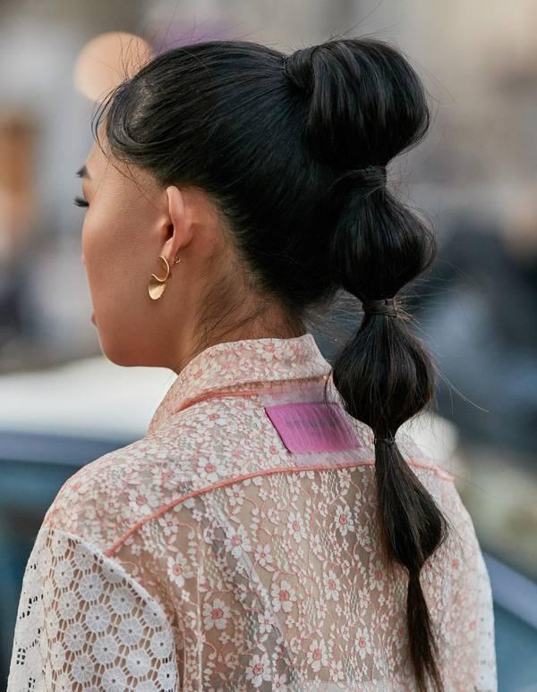 Девушка с необычным высоким хвостиком на темных волосах