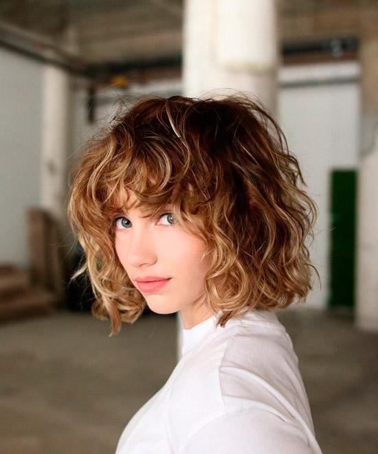 Девушка с пышными кудрявыми волосами с челкой