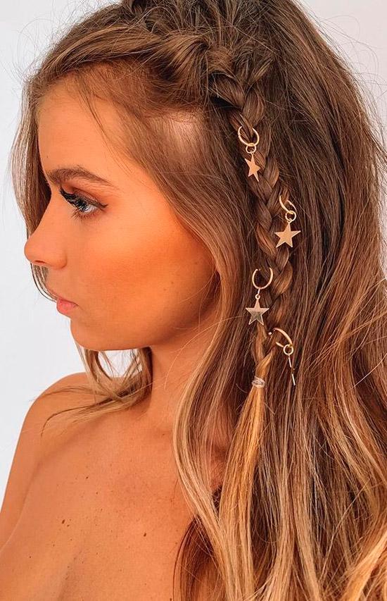 Девушка с русыми волосами с простой косичкой сбоку, украшенная подвесками со звездами