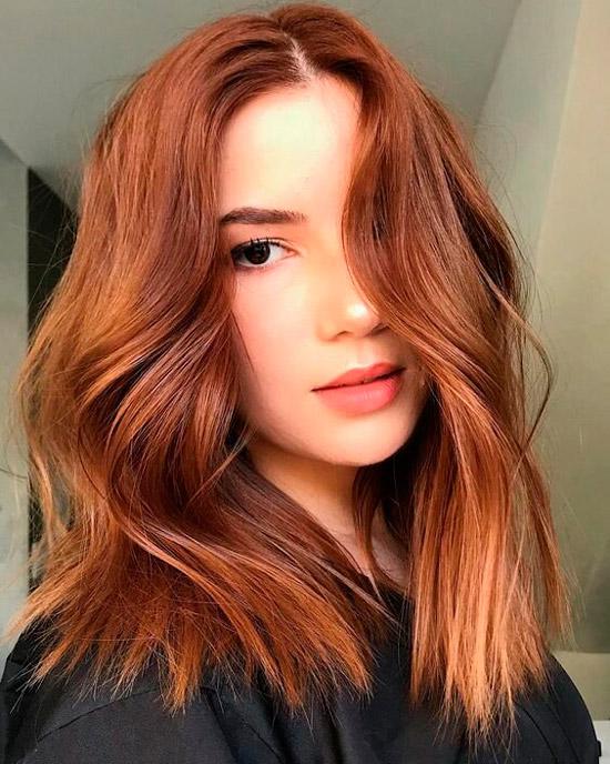 Девушка с рыжими волосами с легкими волнами и пробором по середине