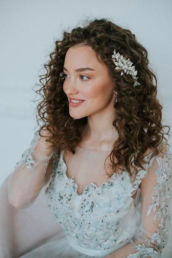 Девушка с шикарными вьющимися волосами с красивой заколкой сбоку