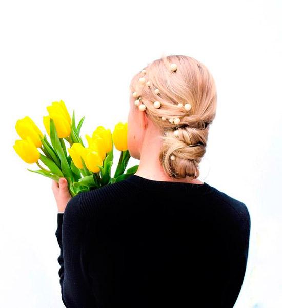Девушка с собранной прической на светлых волосах, украшенная жемчугом