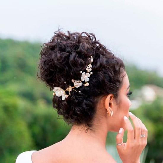 Девушка с темными кудрявыми волосами собранными в высокий пучок с красивыми украшениями