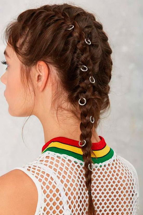 Девушка с темными волосами заплетенные в косы и украшенные простыми колечками