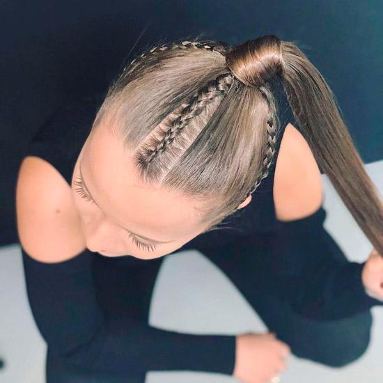 Девушка с тонкими косичками и конским хвостом на длинных волосах
