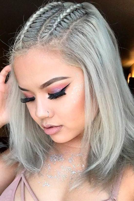 Девушка с удлиненной стрижкой боб на светлых волосах с тонкими косичками