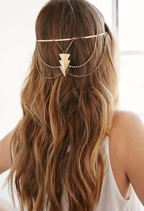 Девушка с ухоженными длинными волосами, украшенные золотыми цепочками
