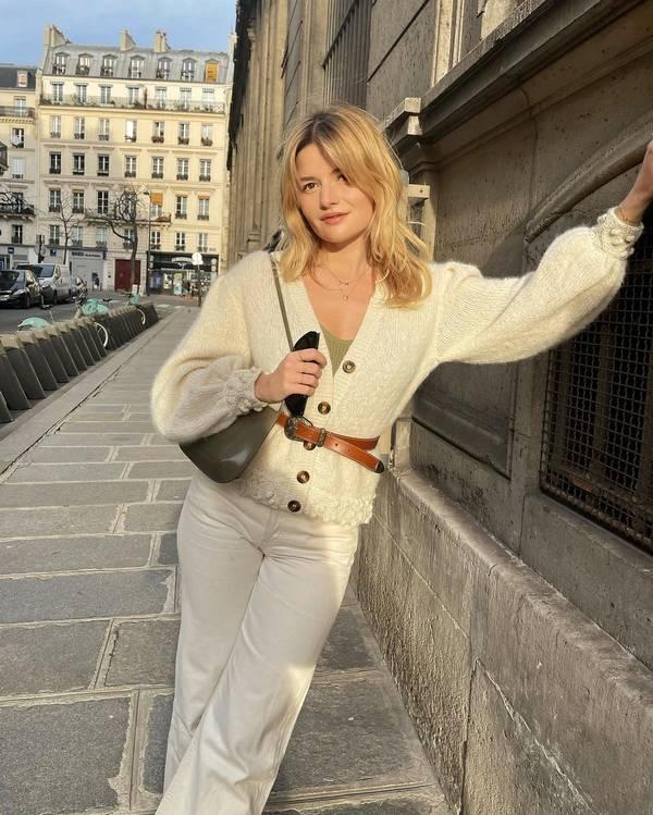 Девушка в белых просторных джинсах, светлый кардиган с ремнем