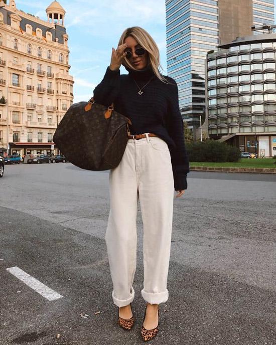 Девушка в белых широких джинсах, черный свитер и леопардовые туфли