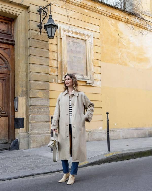 Девушка в бежевом плаще оверсайз, простые джинсы и джемпер в линию