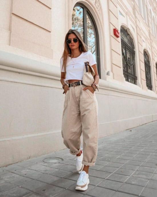 Девушка в бежевых джинсах с ремнем, белый кроп топ и белые кроссовки