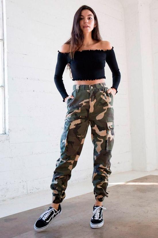 Девушка в брюках хаки, черный кроп топ и кеды