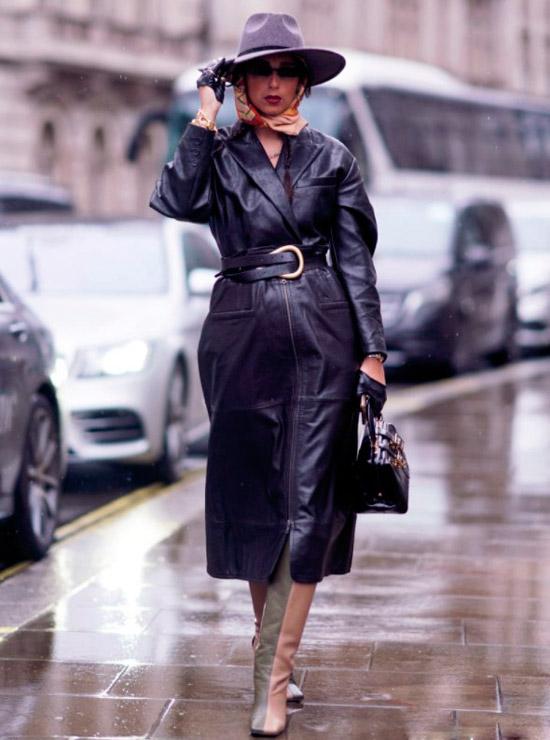 Девушка в черном кожаном плаще с поясом, двухцветные сапоги и серая шляпа защищает от дождя