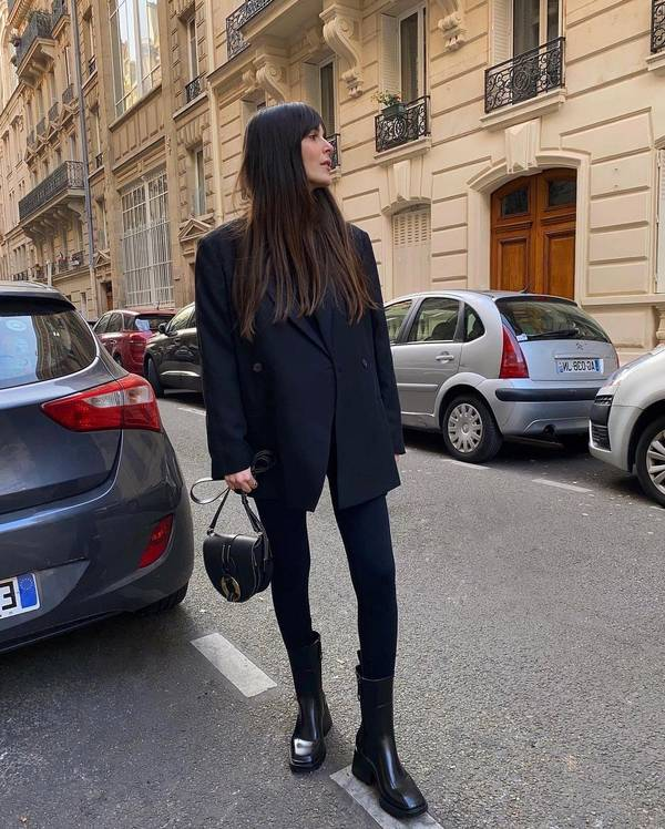 Девушка в черном пиджаке оверсайз, лосины и темные ботинки на толстом каблуке
