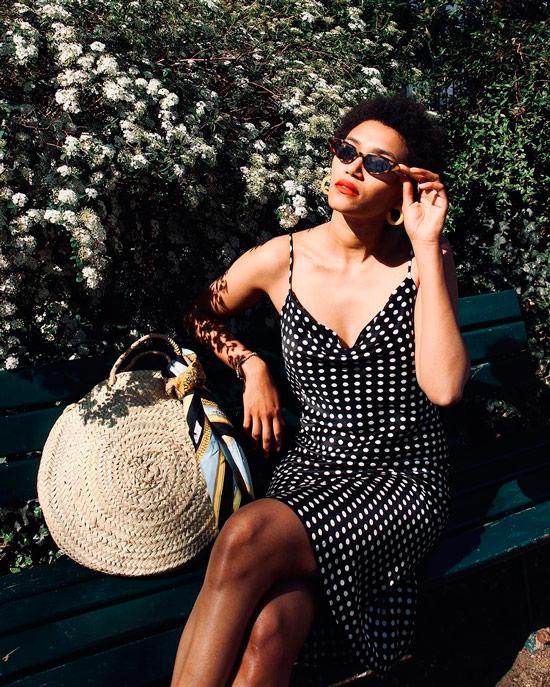 Девушка в черном платье комбинация в горошек, образ дополняет соломенная сумка и солнцезащитные очки