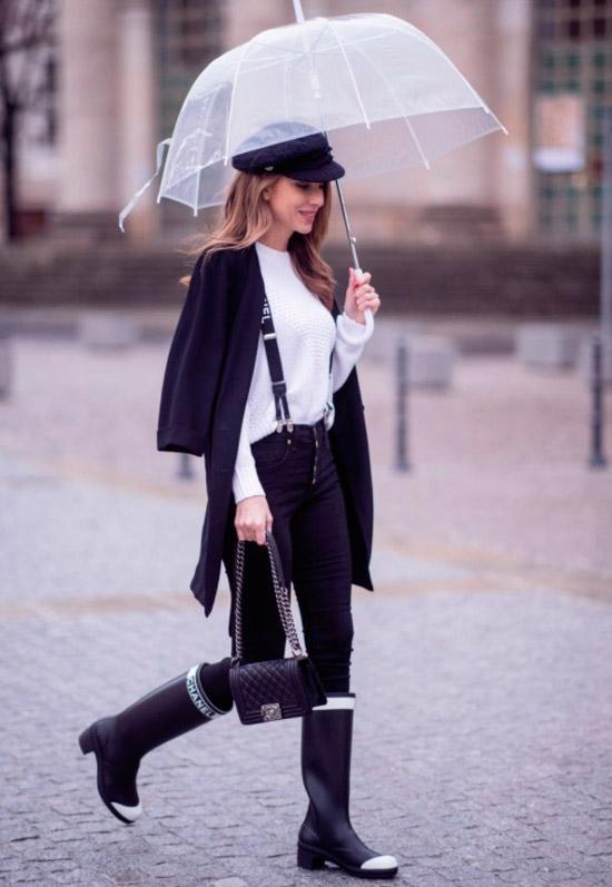 Девушка в черных джинсах скини, белый свитер, черный кардиган, образ дополняют черные резиновые сапоги и небольшая сумочка
