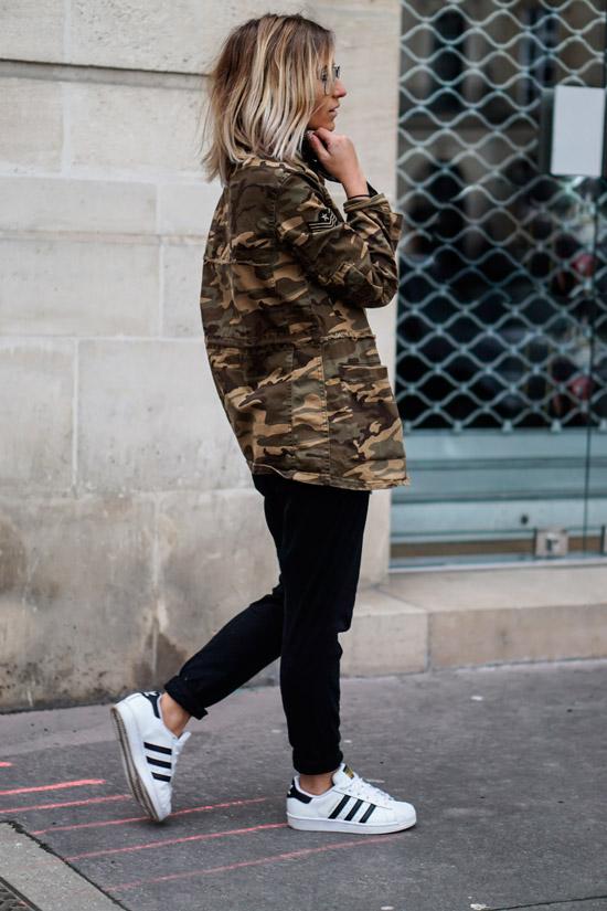 Девушка в черных спортивных штанах, куртка хаки