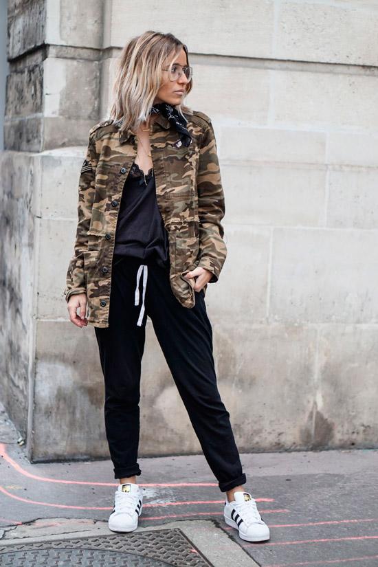 Девушка в черных спортивных штанах, топ и куртка хаки