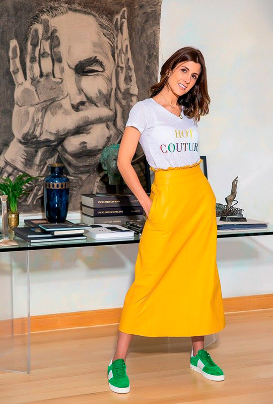 Девушка в длинной желтой юбке, простая футболка с надписью и зеленые кроссовки