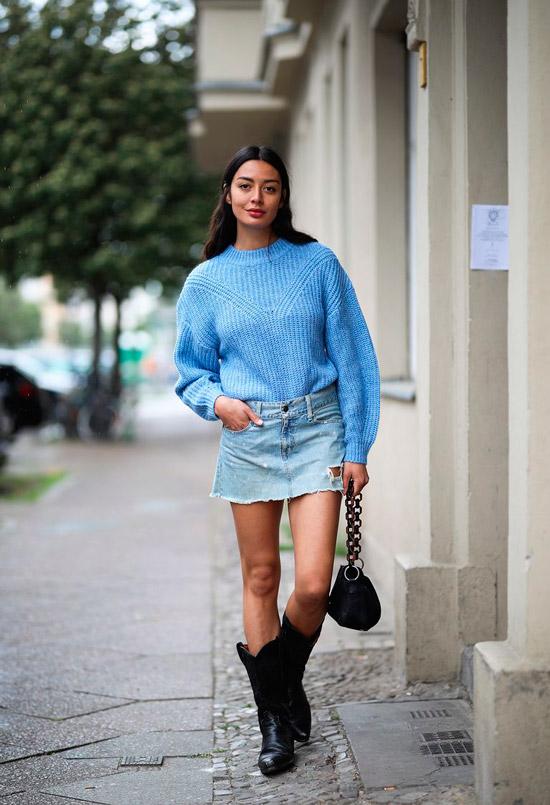 Девушка в голубом свитере, джинсовая мини юбка, образ дополняют черные ковбойские сапоги и черная сумка