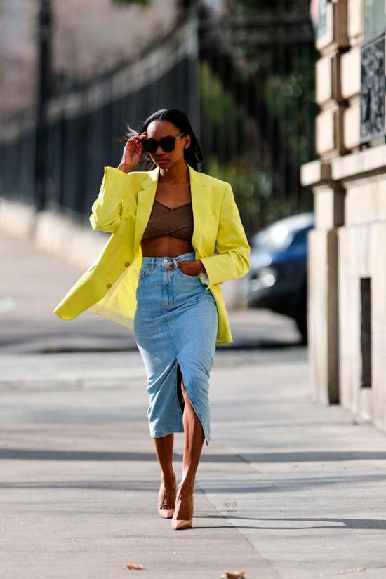Девушка в голубой джинсовой юбке с разрезом по середине, коричневый топ и желтый пиджак оверсайз, образ завершают шикарные туфли на шпильке