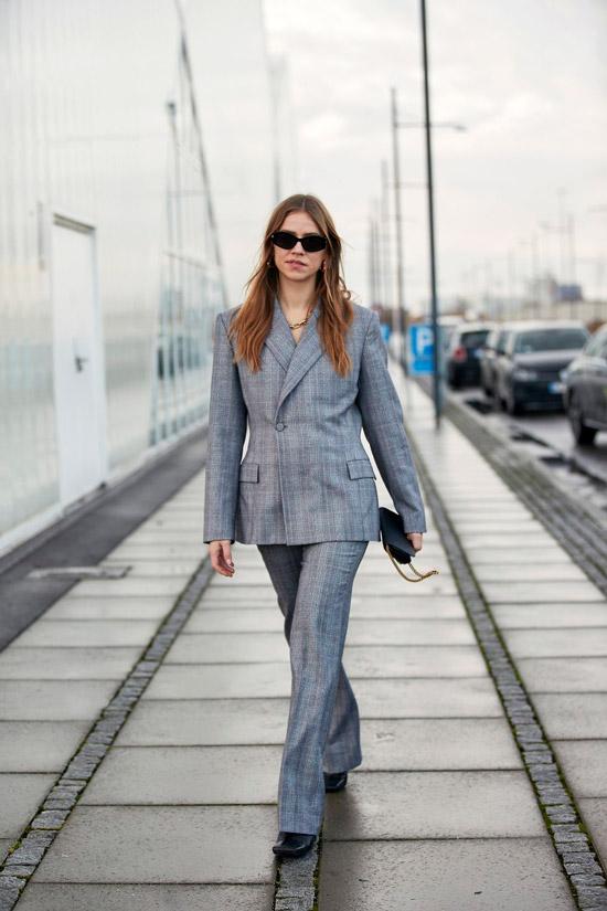 Девушка в классическом сером костюме с приталенным пиджаком, образ дополняют черные туфли, мини сумочка и солнцезащитные очки