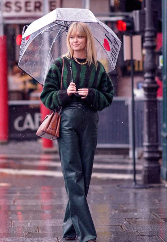 Девушка в кожаных свободных брюках, свитер в черно зеленую полоску и сумочка на плече