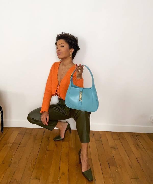 Девушка в кожаных зеленых брюках, оранжевая блузка и туфли на каблуках