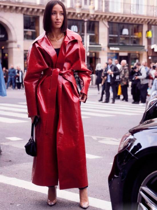 Девушка в красном лакированом плаще с поясом, черная мини сумочка и бежевые туфли