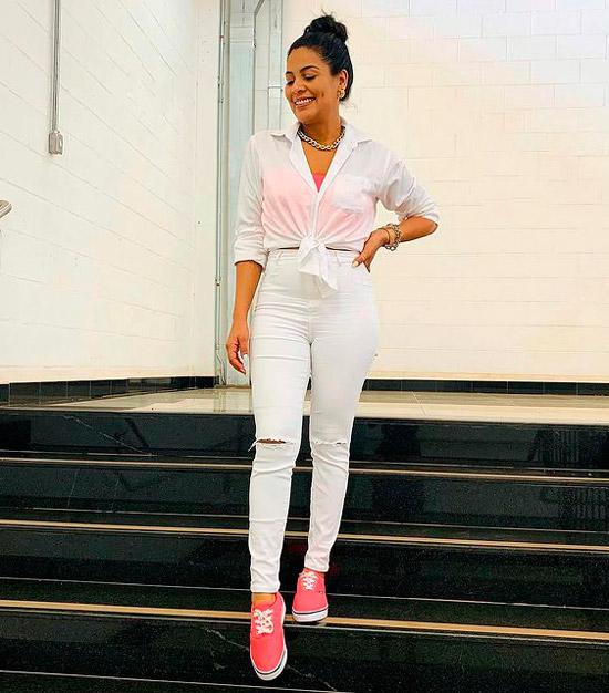 Девушка в облегающих белый джинсах, белая рубашака и розовые кроссовки