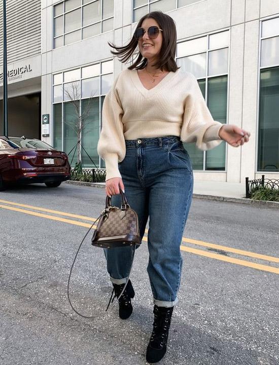Девушка в простых джинсах с завышенной талией, бежевый свитер и черные ботильоны