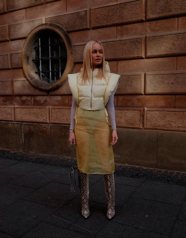 Девушка в прозрачной юбке карандаш, бежевый жилет и сапоги из змеиной кожи