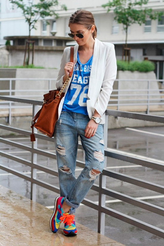 Девушка в рванных джинсах, голубая футболка, белый пиджак и разноцветные кроссовки