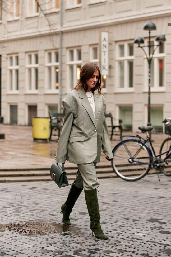 Девушка в сером брючном костюме с блейзером оверсайз, зеленые замшевые сапоги на шпильке и сумочка