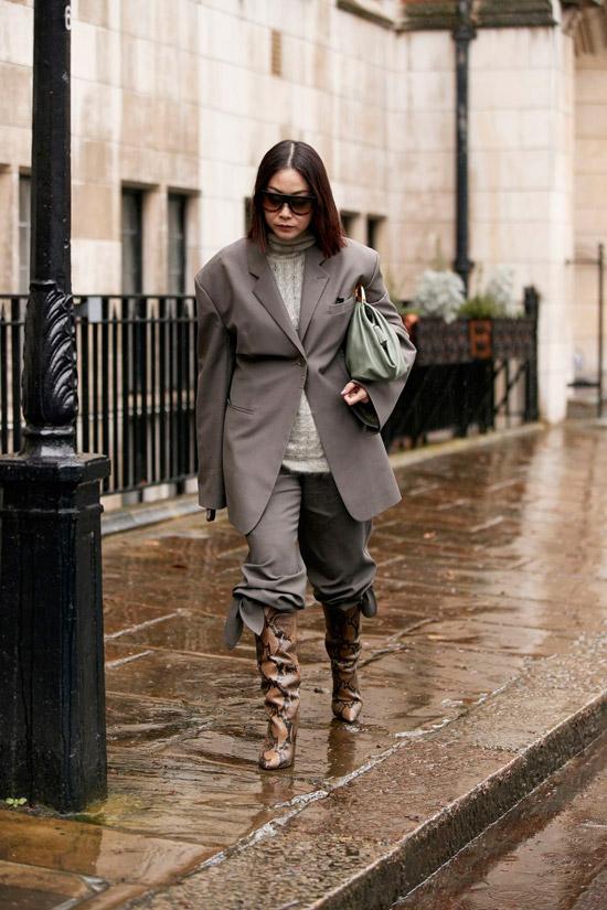 Девушка в сером костюме оверсайз с брюками заправленные в сапоги из змеинной кожи и серая мягкая водолазка