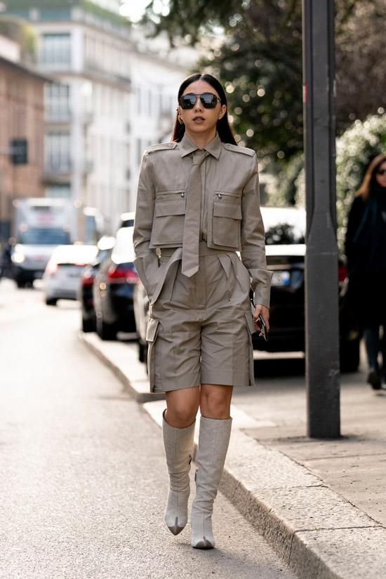 Девушка в сером костюме с шортами бермудами, сапоги молочного цвета на шпильке, образ завершают солнцезащитные очки