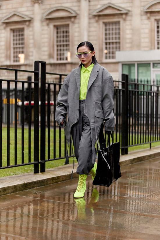 Девушка в сером плаще оверсайз, зеленая рубашка и ботильоны на шнуровке и большая черная сумка завершает образ