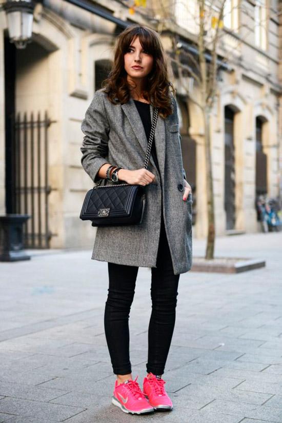 Девушка в сером простом пальто, черные облегающие джинсы и розовые кроссовки