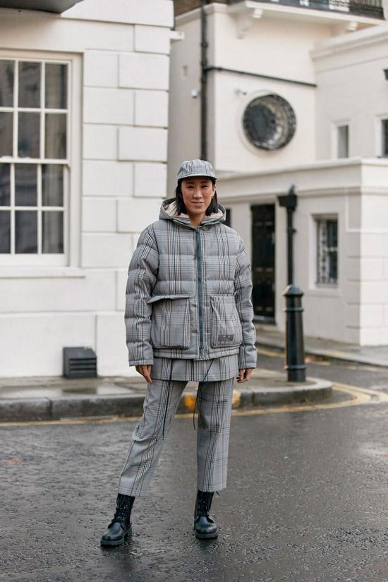 Девушка в сером пуховике в клетку с накладными карманами, укороченные брюки и военные ботинки на шнуровке