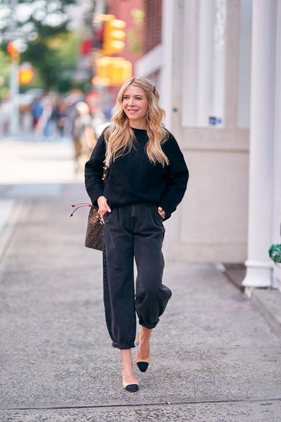 Девушка в широких черных джинсах, черный свитер и туфли