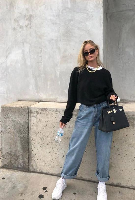 Девушка в широких подвернутых джинсах, черная толстовка и белые кеды