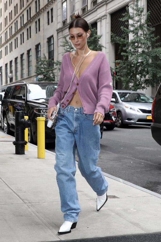 Девушка в широких прямых джинсах, фиолетовый кардиган и белые сапоги