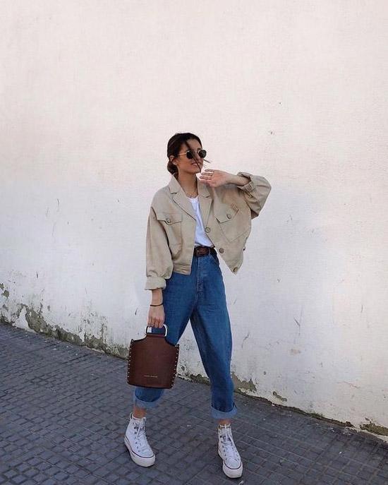 Девушка в широких синих джинсах, бежевый бомбер и белые кеды